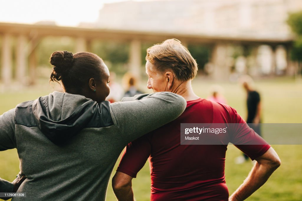 Man and woman talking while looking at senior friends in park : Stock Photo