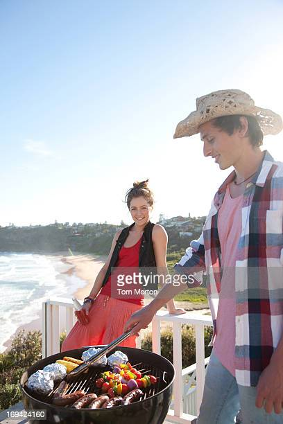 Man and woman tending barbecue with ocean in background