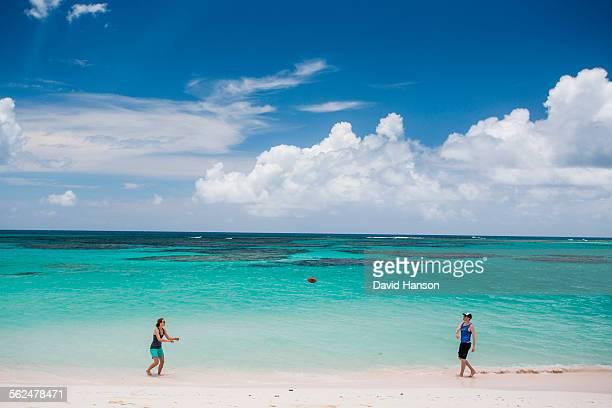 COW WRECK BEACH RESORT, BRITISH VIRGIN ISLANDS, CARIBBEAN. A man and woman throw a football on a white sand beach with teal sea behind.