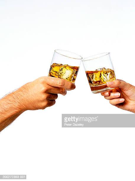 man and woman toasting drinks, close-up - brindisi bicchieri foto e immagini stock