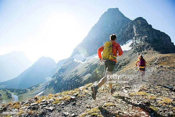 man and woman trail running, lewis range, rocky mountains, glacier national park, usa - cross country running stock pictures, royalty-free photos & images