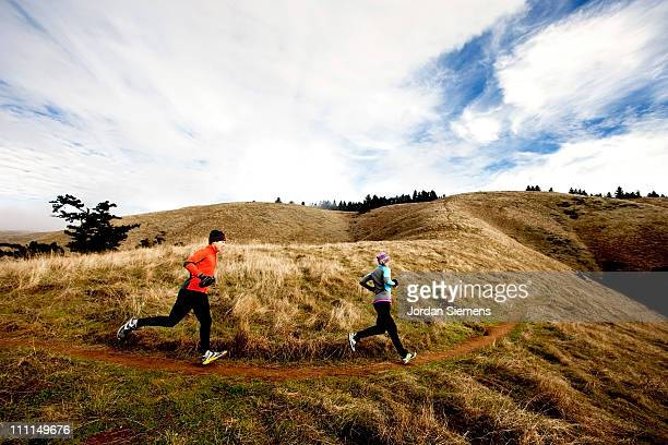 A man and woman trail running.