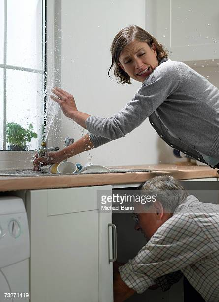 man and woman trying to fix sink in kitchen - spraying stock pictures, royalty-free photos & images