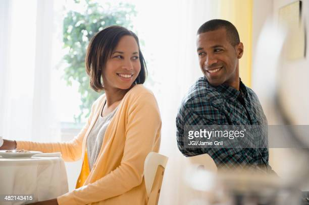 Man and woman turning to smile at each other in restaurant