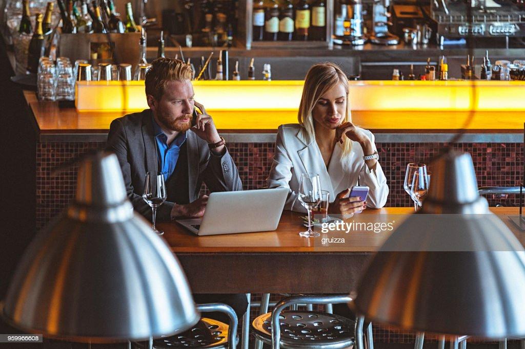 Mann und Frau nutzen ihr Smartphone während der Sitzung zusammen für die Tabelle in der Mittagszeit in ein Cafe / Restaurant : Stock-Foto