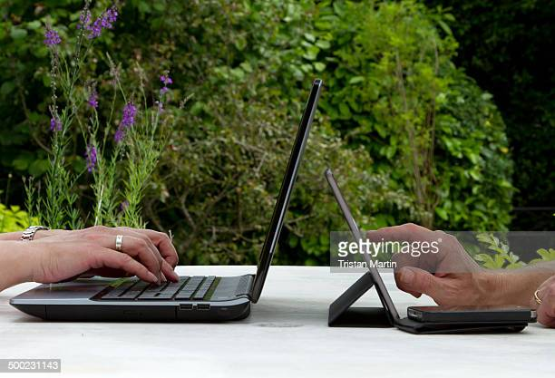 A man and woman using a laptop computer tablet computer and smartphone on a garden table in summer