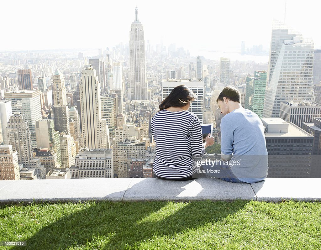 man and woman using digital tablet in city : Stock Photo
