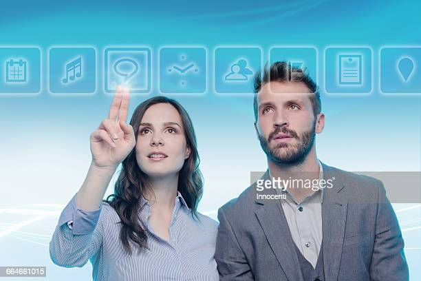 man and woman using graphical screen, woman touching icon - gui stock pictures, royalty-free photos & images