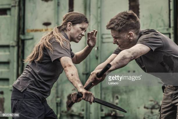 man and woman using krav maga self defense in grimy outdoor urban setting - fighting stance stock pictures, royalty-free photos & images