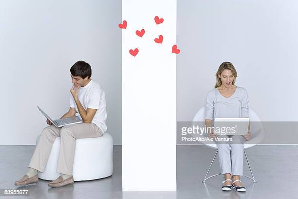 man and woman using laptop computers, hearts floating in the air between them - online dating stock pictures, royalty-free photos & images