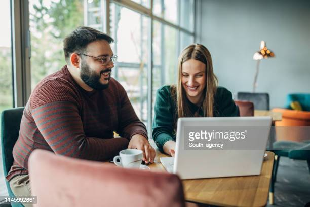 man and woman using laptop in cafe - fat woman sitting on man stock pictures, royalty-free photos & images