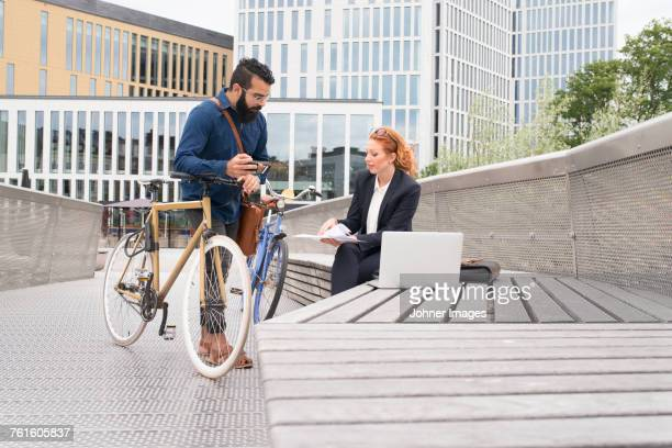 Man and woman using laptop outdoors