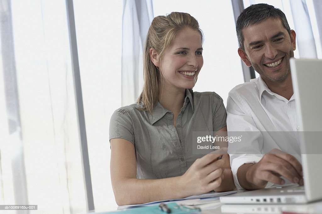 Man and woman using laptop : Stockfoto