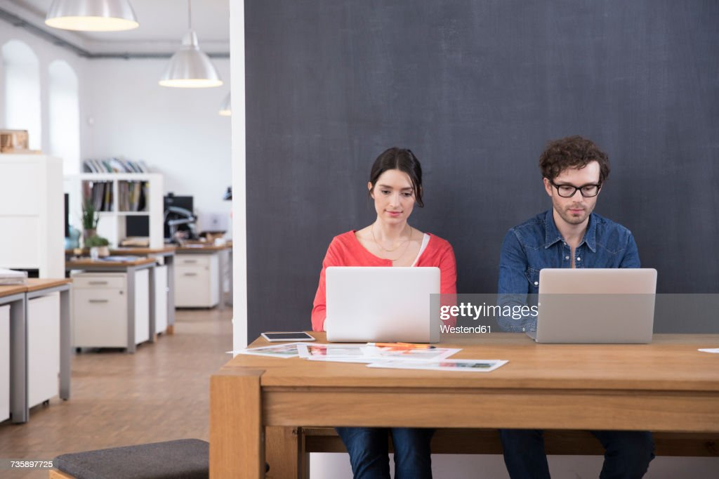 Man and woman using laptops on table in office : Foto de stock