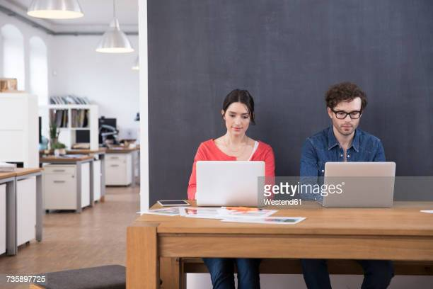 Man and woman using laptops on table in office