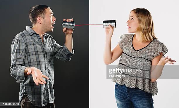 Man And Woman Using Tin Can Phones