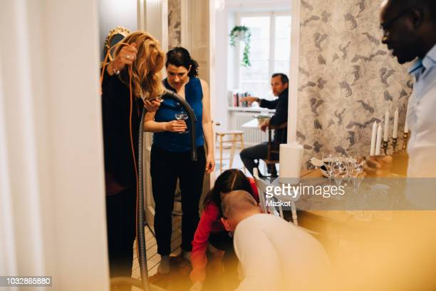 man and woman using vacuum cleaner while friends standing by table at home - cleaning after party bildbanksfoton och bilder