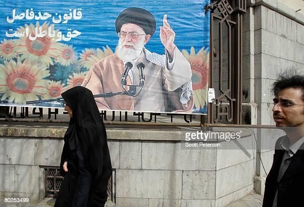 A man and woman walk past a banner of supreme leader Ayatollah Sayed Ali Khamenei as Iranians vote in elections for the 8th majlis or parliament...