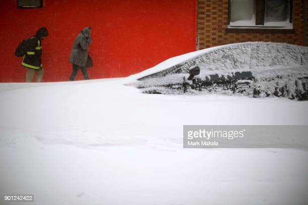 A man and woman walk past a car buried by the snow on January 4 2018 in Atlantic City New Jersey A Òbomb cycloneÓ winter storm has caused every East...