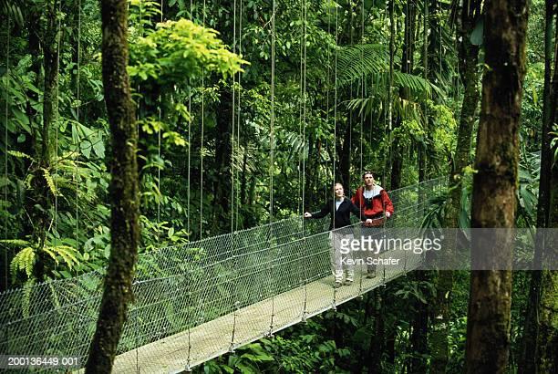 Man and woman walking across footbridge in rainforest