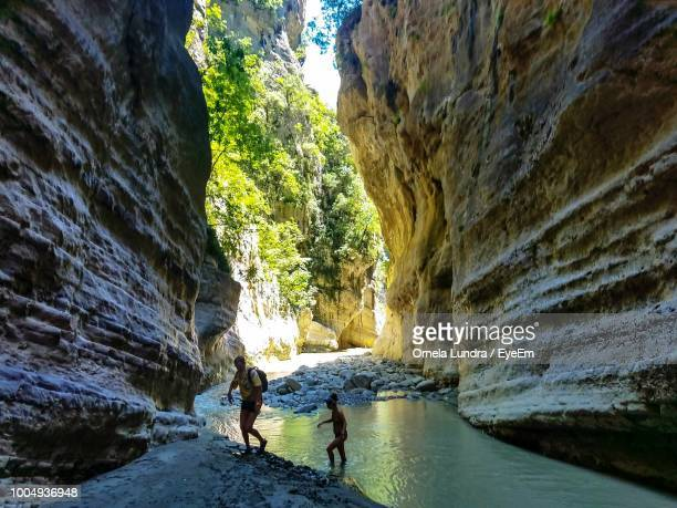 man and woman walking amidst rock formation in lake - albania stock-fotos und bilder