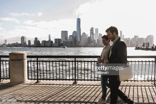 USA, man and woman walking at New Jersey waterfront with view to Manhattan