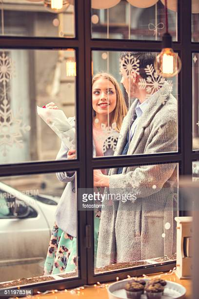 Man and woman walking by cake shop