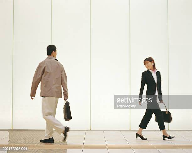 Man and woman walking down corridor, looking over shoulders, side view