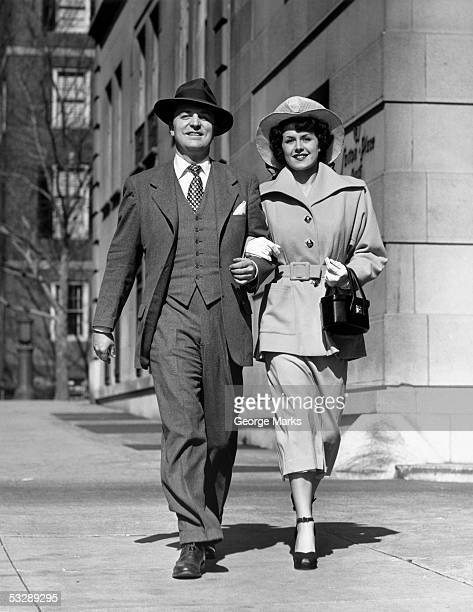 man and woman walking down street - fedora stock pictures, royalty-free photos & images
