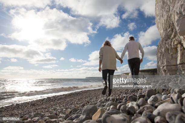 Man and woman walking hand in hand along beach