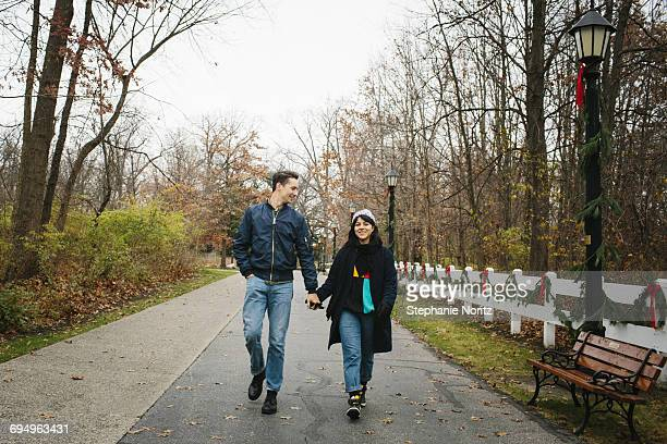 man and woman walking in park holding hands - ohio stock pictures, royalty-free photos & images