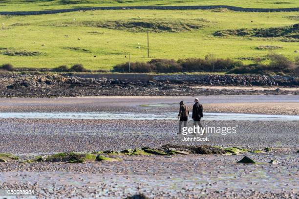 Man and woman walking on a quiet beach