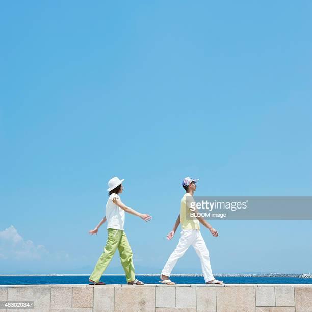 Man And Woman Walking On Breakwater