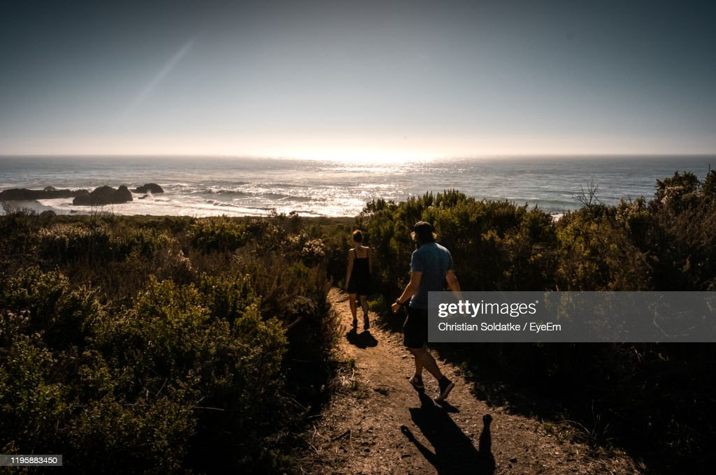Man And Woman Walking On Land Against Sea And Sky : Stock-Foto