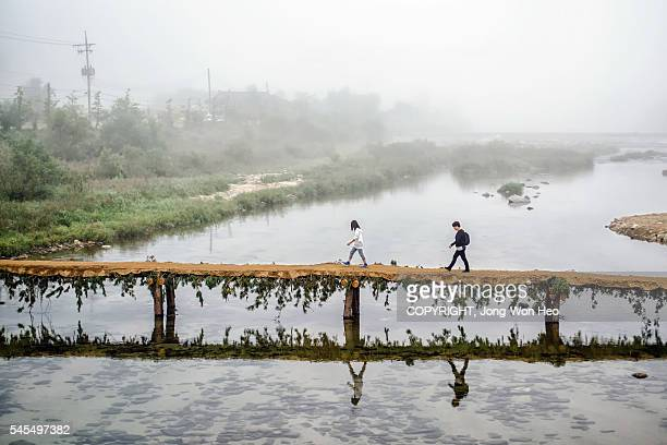 A man and woman walking on the bridge over the brook in the morning