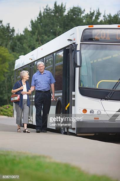 A Man And Woman Walking To Get On A City Bus