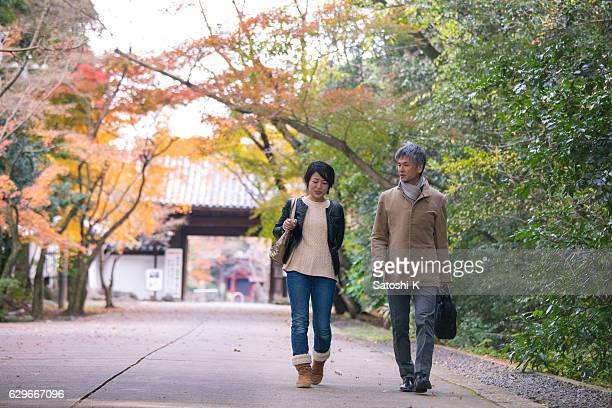 Man and woman walking together under autumn foliage