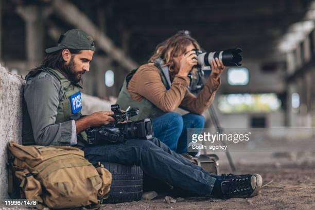 mann und frau kriegspresse macht eine pause in verlassenen gebäude - reporterstil stock-fotos und bilder