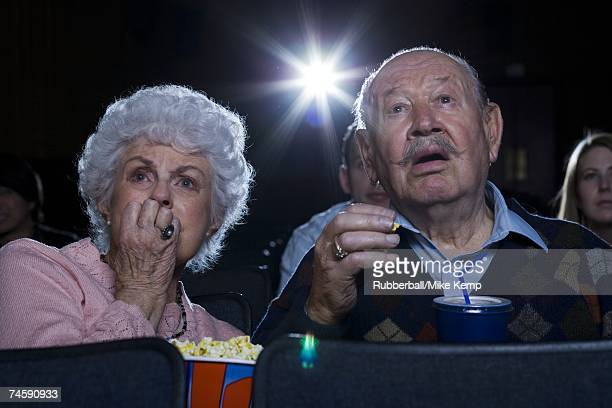 Man and woman watching film at movie theatre frightened