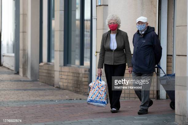 Man and woman wear face coverings in the town centre on September 24, 2020 in Merthyr Tydfil, Wales. Four more counties in south Wales went into...