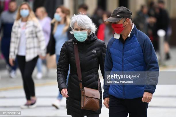 A man and woman wear faces masks on Queen Street on October 4 2020 in Cardiff Wales A local lockdown came into force for Cardiff on September 27 amid...