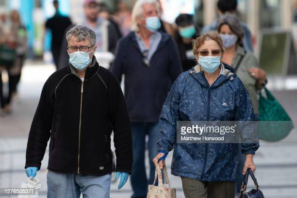 Man and woman wear surgical face masks on Queen Street on September 23, 2020 in Cardiff, Wales. Four more counties in south Wales went into local...