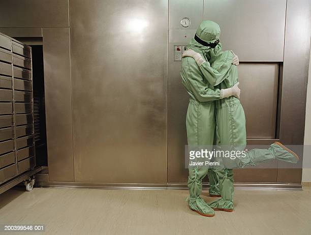 man and woman wearing boiler suits embracing - protective suit stock pictures, royalty-free photos & images
