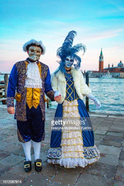 Man And Woman Wearing Costume And Mask Against Gondolas During Venice Carnival
