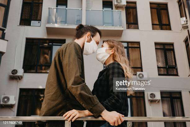man and woman wearing face protective medical mask on street. - micro organism stock pictures, royalty-free photos & images