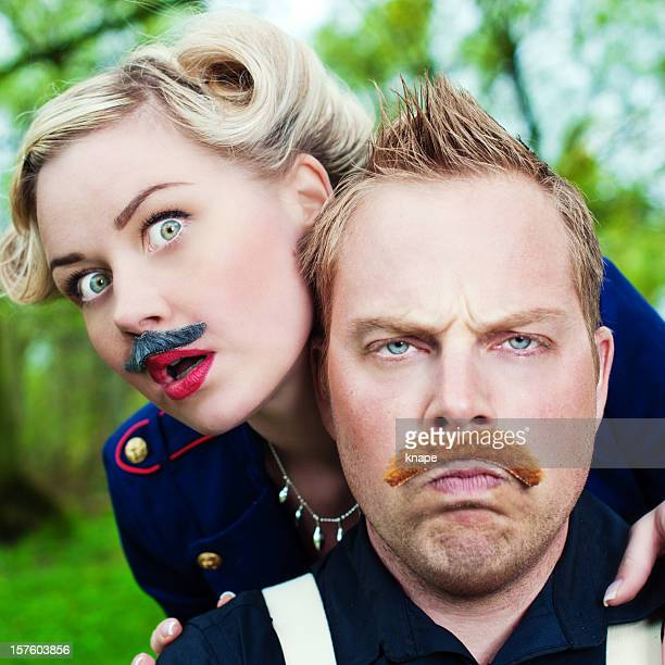 Man and woman wearing fake mustaches