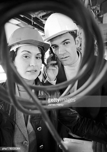 Man and woman wearing hard hats, portrait, b&w