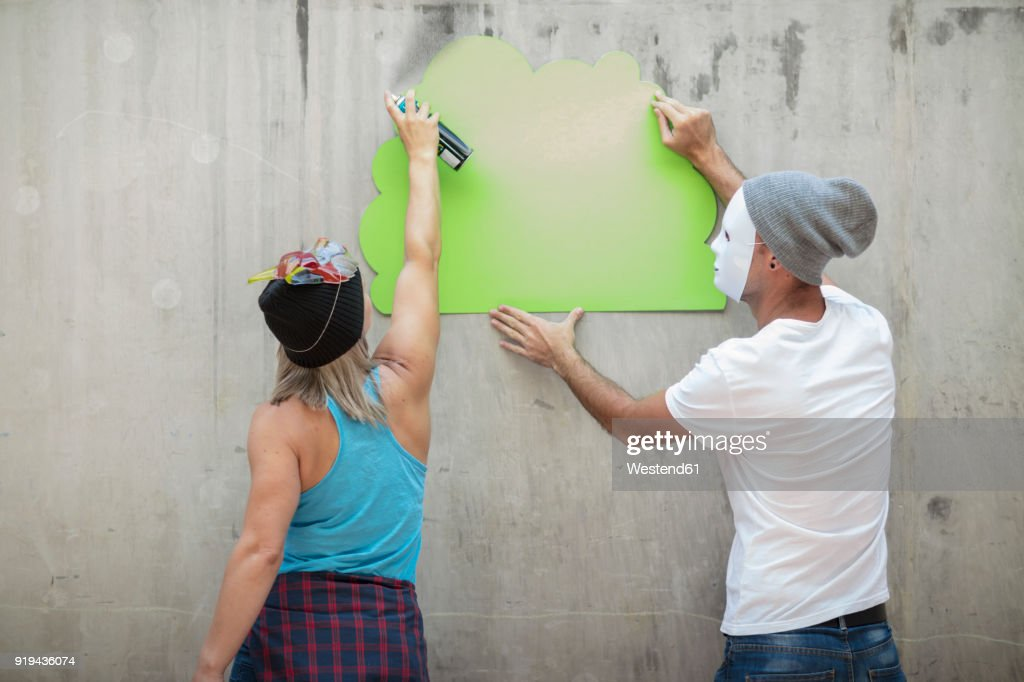 Man And Woman Wearing Masks Spray Painting A Concrete Wall