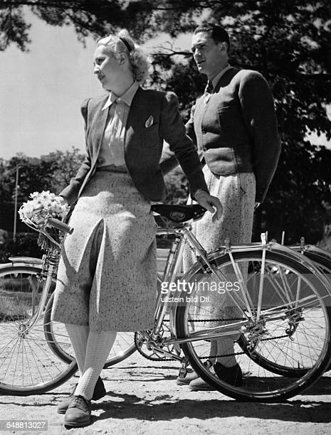 Man and woman wearing matching clothes for riding a bicycle - undated - Photographer: Gyula H. Brassai - Published by: 'Die Dame' 13/1938 Vintage...
