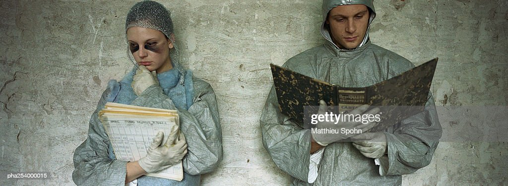 Man and woman wearing protective suits, examining documents : Stockfoto
